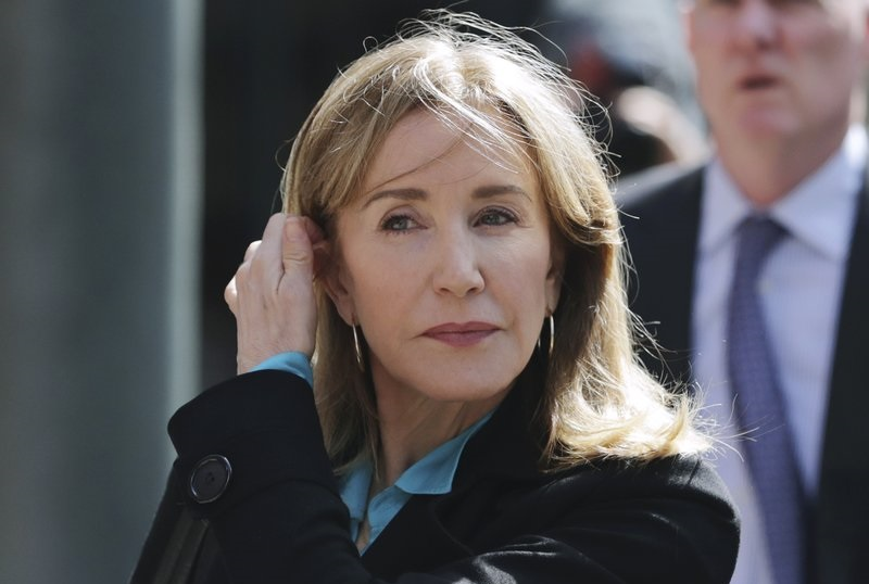 FILE - In this April 3, 2019 file photo, actress Felicity Huffman arrives at federal court in Boston to face charges in a nationwide college admissions bribery scandal. On Monday, May 13, 2019, Huffman is expected to plead guilty to charges that she took part in the cheating scam.