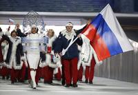 FILE - In this Feb. 7, 2014 file photo Alexander Zubkov of Russia carries the national flag as he leads the team during the opening ceremony of the 2014 Winter Olympics in Sochi, Russia. At left is model Irina Shayk carrying the Russian placard.